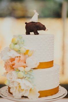 Beautiful wedding cake with sugar flowers and the cutest cake topper - a bunny sits atop a grizzly bear #caketopper #wedding #weddingcake