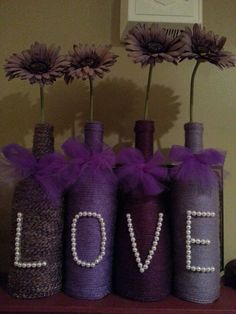 Shades of purple yarn wrapped LOVE wine bottles with pearl and tulle accents.