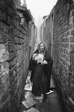 Liverpool Slums, November 1956  An elderly woman standing among the litter in a back alley of the Liverpool slumsPhotograph: Thurston Hopkins/Picture Post/Getty Images