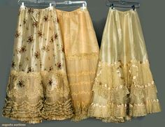 Three Belle Epoque Silk Petticoats, c1900; All ivory with multiple layered deep hem flounces: Two with flounces of Valenceinnes lace and ivory satin ribbons; one printed with delicate floral baskets and Valenciennes lace