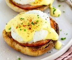 Easy eggs benedict breakfast with poached eggs on top of toasted English muffin, savory Canadian bacon, and drizzled with hollandaise sauce.
