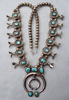 Navajo Squash Blossom Sterling & Turquoise Vintage Necklace. This Navajo Squash Blossom Necklace is from the 50's and a real beauty! About 30 inches of sterling silver beads with a double row behind the Squash Blossoms. Six blossoms are on each side with beautiful detailing around the Turquoise. $1,200.00.