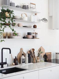 Modern Scandinavian kitchen, black and white interior design with green plants.