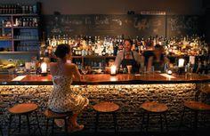 Caged rocks, live-edge walnut, and flickering candles set the scene for Kask's spirit-driven cocktails. Image: Stuart Mullenberg