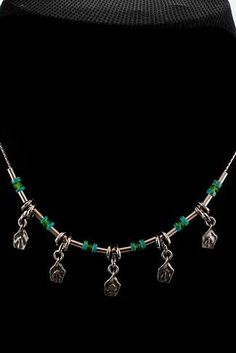 Commentary Necklace    Hand made, sterling silver necklace with mix of Turquoise and Peridot stones necklace.    Chain: 16 in. long; Pendent: 0.8 in. long, 0.25 in. wide.  Price: $98.00