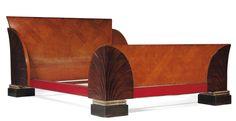 MARCEL COARD (1889-1975) Lit En placage de palissandre,érable moucheté et bois teinté noir sur une âme en chêne.La tête et le piètement cintré sont soulignés de larges motifs en palmes stylisées et d'un bandeau laqué rouge à jonc de métal chromé.Il repose sur des piètements cubiques teintés noir à double rang de cordelières patiné argent.Vers 1930. H:97 cm L:214 cm P :159 cm Bibliographie:modèle reproduit dans:Anne Bony Les années 30 Editions du Regard 1987 page 948.Art et Décoration
