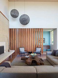 A sala é uma só para dois ambiente mas com o brise de madeira a sala de jantar esta delimita e ligeiramente reserva Uma solução fácil e de grande impacto visual.
