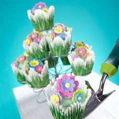 Springtime is the theme of this pretty cupcake display. Easy to make, the cupcakes are baked in grass baking cups, iced in buttercream icing and topped with Multi Flower Icing Decorations. Display them on the Cupcakes-N-More Stand at your Easter or spring celebration!