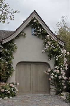 Muted brown A-frame house with climbing roses