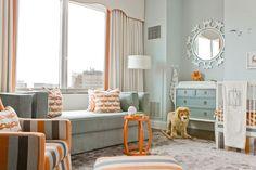 How sweet is this room?   gray blue walls; ivory drapes orange trim; ivory cornice box orange trim; gray blue velvet sofa; gray orange striped glider ottoman; white crib; blue gray changing table dresser; white round mirror