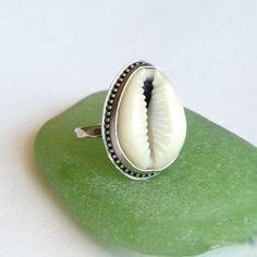 A natural, sea tumbled Cowrie Shell set in a fine silver bezel. Oxidized for a vintage bohemian look that brings out the textures in the ring. Hammered textured band Made to order in your size. Spirit