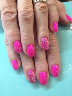 Pink polish with glitter ring fingers over acrylic nails