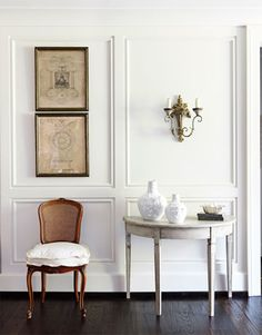 """Jonny Valiant  Back Next  View Thumbnails  White and Antiques  In the entry, Schnell and Davis painted the walls China White by Benjamin Moore. The white sets off a Swedish demilune table and French pen-and-inks. """"Using variations of white adds textures and layers and gives the house an ethereal feeling,"""" Schnell says."""