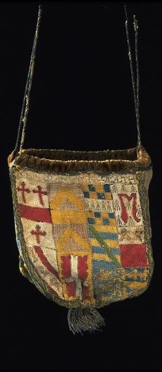 Purse, made in England, ca 1540 -- This formal, heraldic purse associated with marriage has more significance than a purse used simply for money, or a 'swete-bag' used for carrying perfumed herbs to sweeten the atmosphere. Both men and women carried or wore pouches or purses. The long strings of this example suggest that it was intended to hang from the waist. English purses of this date are extremely rare.