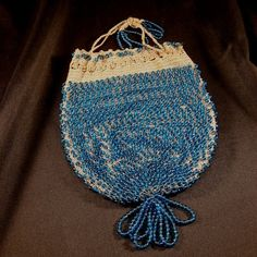 Transparent Teal glass bead were incorporated into this flapper era reticule hand bag. Rather sizable round beads in comparison to most beaded purses from the 1920's, they are evenly spaced incorporated around the purse with crochet stitching in-between.