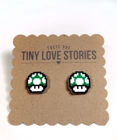 This is a tiny love story for Super Mario. The infamous 1-Up Mushroom is the ultimate life saver in the classic video game and now you can wear them on your ears!     The earrings are made of a hard durable plastic.     These measure approx. 1/2 inch by 1/2 inch. A little smaller than a dime.