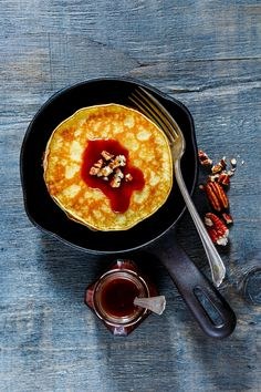 Stack of american pancakes - Top view of tasty pancakes with pecans and chocolate caramel sauce on vintage cast-iron frying pan over rustic wooden background. Delicious dessert for breakfast