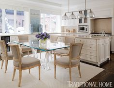 Custom cabinetry and countertops lighten up the kitchen, while the glass table with acrylic base keeps the space light and airy. - Photo: Werner Straube / Design: Gail Plechaty