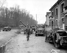 U.S. Army Pvt. Jackson, of the 95th Infantry Division, assigned to XX Corps, Third United States Army (United States Army Central), walks through the suburbs of Metz during the Battle of Metz as a U.S. Army convoy passes by on the left. In front of the houses several jeeps are stationed, as well as a somewhat shielded U.S. M8 Armored Gun System light tank and an abandoned German 8.8 cm Pak 43 anti-tank gun. Saint-Julien-lès-Metz, Moselle, Grand Est, France. November 1944.