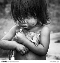 Küçük Guarani kız, ölü bir sıçanı elinde tutarken.