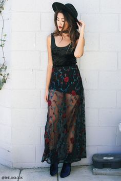 A semi-sheer mesh maxi skirt featuring floral embroidery and a concealed back zipper. Matching top available.