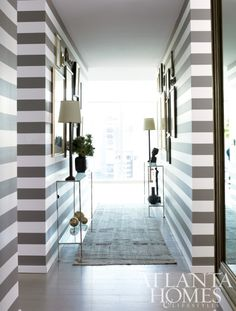 This hall features elegant and classy striped gallery walls with two slim console tables. I love it...V