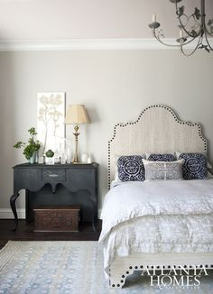 Unique shapes, like this curved nailhead headbaord and carved console bedside table, make this bedroom the perfect retreat for visitors.