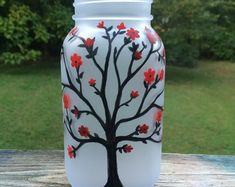 Frosted glass votive holder or vase. Hand painted tree with red flowers. Excellent option for organization as well to hide or store you personal items. Painting Glass Jars, Painted Glass Vases, Painted Wine Bottles, Bottle Painting, Painted Spoons, Tree With Red Flowers, Red Tree, Diy Flowers, Mason Jar Vases