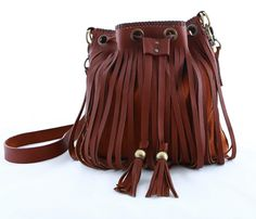 The 'Mockingbird' by KONOC is a stylish brown suede and leather fringed shoulder/cross body bag with an inside pouch pocket, drawstring closure through oversized eyelets and leather tassel details.