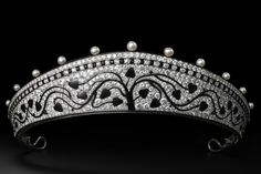 High resolution image of A kokoshnik style tiara created by Cartier Paris in 1914. This platinum piece is set with old-cut round diamonds, 15 natural pearls, calibrated and fancy-shaped onyx and black enamel.