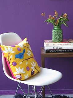Purple wall, yellow pillow.