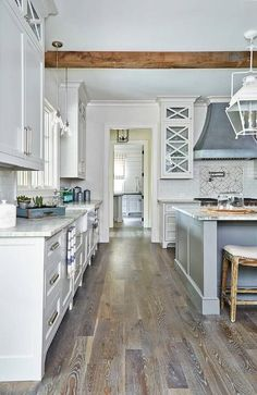 Rustic kitchen boasts a zinc hood mounted against above a Wolf range white glazed subway backsplash tiles framing mosaic cooktop tiles located above a stainless steel range.