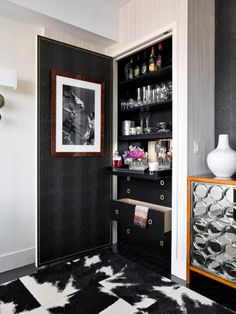 We took an underutilized closet and turned it into a bar by lining it with faux croc wallpaper, then adding studs and a framed photo to the back of the door. The built-in drawers were dressed with vintage brass pulls and sprayed in black lacquer while the tray, outfitted with drawer glides, was lit from the shelf above. — Robert Stuart, owner, Robert Stuart Interiors