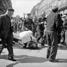 Original caption:Resistance Roundup. Paris, France: Lying wounded in the street, a German officer gets the attention of a Red Cross worker as French patriots round up Nazis and collaborators after street fighting in liberated Paris. Resistance snipers still terrorize the populace of the French capital. The Allies have left the job of restoring order to the French. August 28, 1944.