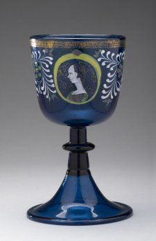 1450 - Goblet; blue glass; straight-sided bowl resting on stem with flattened knop and folded bell-foot; bowl painted with enamels; two oval medallions outlined in yellow enclosing with male and female portraits; sides ornamented with foliate design, white, green and pink; three gilt bands around rim.