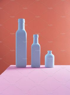 Three bottles organized in a descending order over pink and orange background Still Life Photographers, Orange Background, Bottles, Water Bottle, Organization, Stock Photos, Drinks, Getting Organized, Drinking