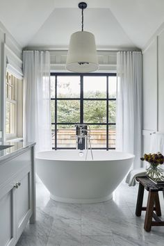The tub floats right in front, positioned so the clients can enjoy a bubble bath with a breeze | archdigest.com