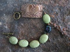 """Bracelet 7.5"""" lime Howlite and scarab beetle beads with brass bird stamping and toggle clasp.. $25.00, via Etsy."""