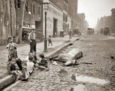 Playing children near dead horse, New York, ca 1900. Photographer unknown.
