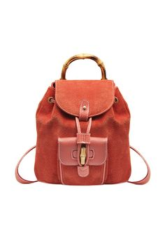 A small vintage Gucci backpack from the iconic Bamboo series in scarlet suede and leather. The backpack fastens with a strap and a flap. One exterior flap pocket and a bamboo handle. Adjustable shouder straps.
