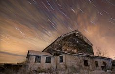 """A Haunted Trail"" by Joshua Debner ~ The combination of clouds and stars moving across the sky, placed behind an abandoned home, make this photo by Joshua Debner extra-eerie. ""This is around a 30 minute exposure stacked with 1 minute exposures. As you can see it was a little bit of a foggy/cloudy day, but I think it helped make the photo interesting."" Pintwist on another kind of light in the sky."