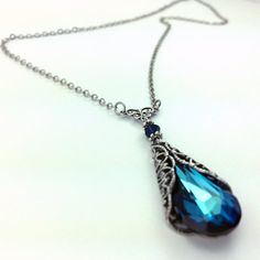This beautiful silver plated necklace features a Swarovski Elements Bermuda Blue crystal pendant encased in a lovely filigree wrap, and topped