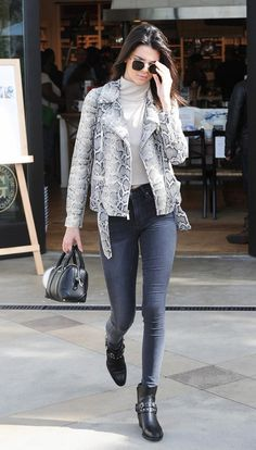 Kendall Jenner wears a cropped turtleneck sweater, snakeskin moto jacket, skinny jeans, ankle boots, mini Givenchy satchel, and aviator sunglasses