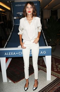 Alexa Chung wears a white button-down shirt with white cropped skinny jeans and black and white shoes