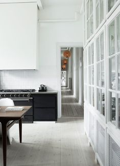 In a modern well lit bright white home, a bit of black in the kitchen adds just the right amount of contrast. Don't be shy when it comes to black-and-white in the kitchen whether in a traditional or modern space, black-and-white is timeless and versatile as seen here with white walls and floors and black appliances and base cabinets.