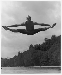 Jason Statham- idea of subject in motion, in mid air over body of water black and white, trees in distance