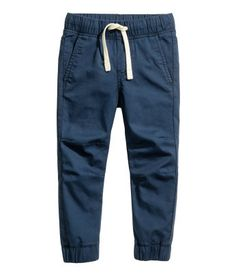 Dark blue. Pull-on pants in woven cotton fabric. Elasticized drawstring waistband and side pockets. Tapered legs with seams at knees and wide elastication