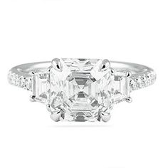 Elegant three stone engagement ring with asscher cut center diamond offset by matching trapezoid step cut side-stones.  Notice the beautiful pave work along the band and low profile appearance; handmade in platinum