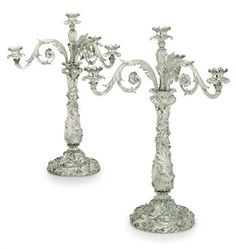 A PAIR OF GEORGE IV SILVER FOUR-LIGHT CANDLEABRA  MARK OF BENJAMIN SMITH, LONDON, 1822 AND 1823  The domed bases each cast with robust foliage scrolls and flowers, with a similarly cast baluster stem, the detachable branches each with three reeded and foliage scroll arms terminating in a socket with detachable rocaille nozzle, with a further central socket, each socket engraved with two crests with a baron's coronet between, marked on base, on branches and each nozzle  24 in.  high  417 oz.