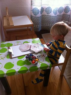 A new craft table. An IKEA lack table covered in oilcloth. by repurposed playground, via Flickr